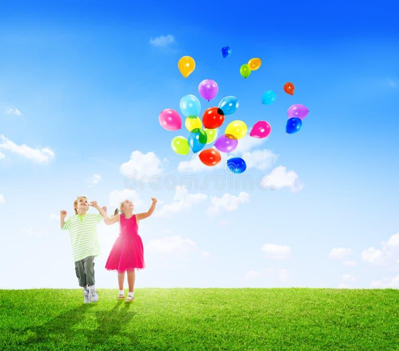 Vrolijke Kinderen die Ballons in openlucht spelen royalty-vrije stock afbeeldingen