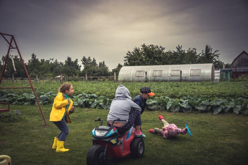 Vrolijke kinderen die pret in openlucht speelplaats hebben tijdens de zomervakantie die in platteland gelukkige jonge geitjes onb stock fotografie