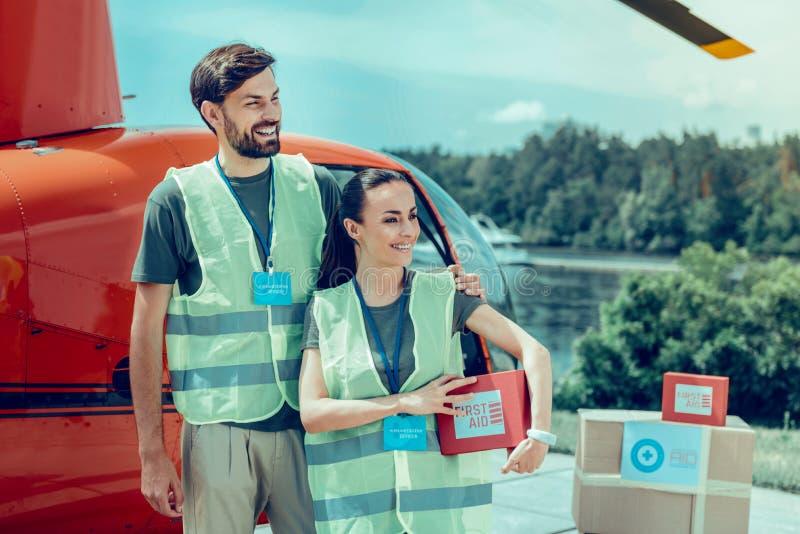 Vrolijke knappe bedrijvige vrijwilligers die met dozen worden omringd stock foto