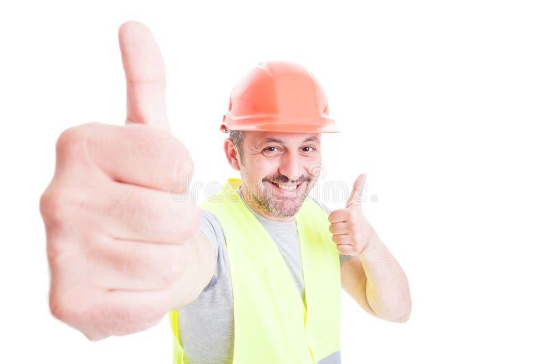 Vrolijke knappe bouwer die dubbele duim op gebaar doen stock fotografie