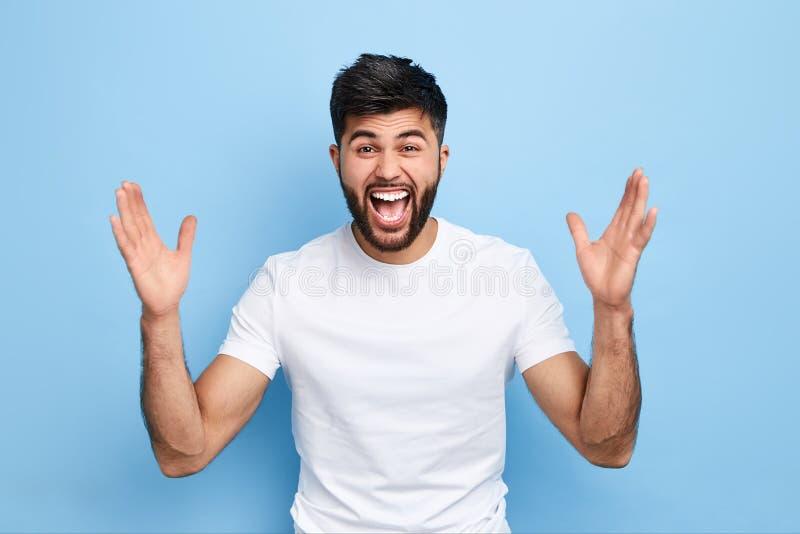 Vrolijke knappe gelukkige kerel die zijn handen omhoog opheffen stock foto