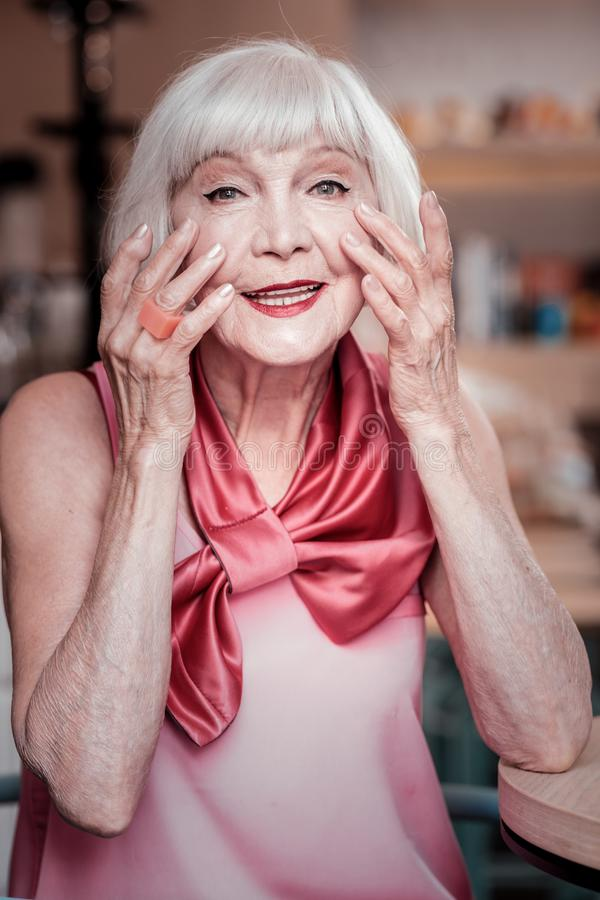 Vrolijke knappe hogere dame die in zijdeblouse skincare producten toepassen royalty-vrije stock afbeeldingen