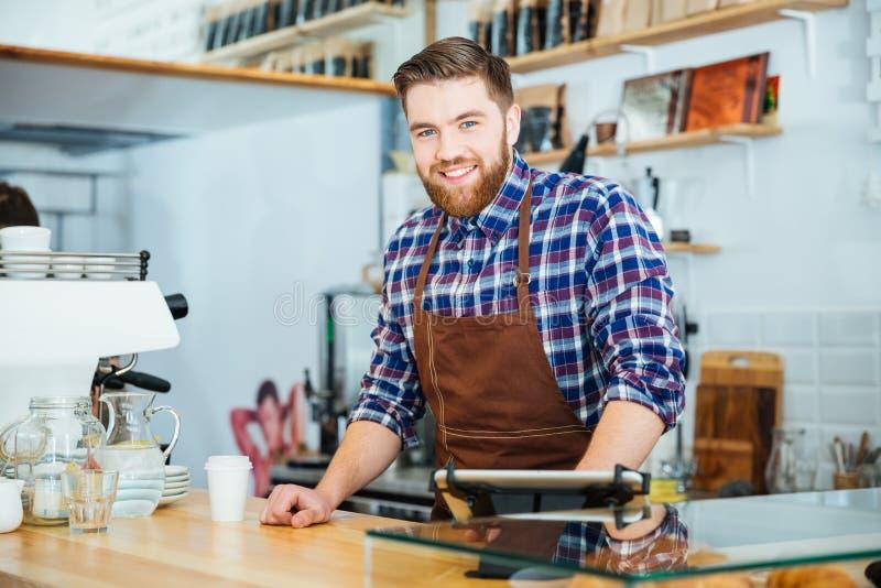 Vrolijke knappe jonge barista met baard die in koffiewinkel werken royalty-vrije stock afbeelding