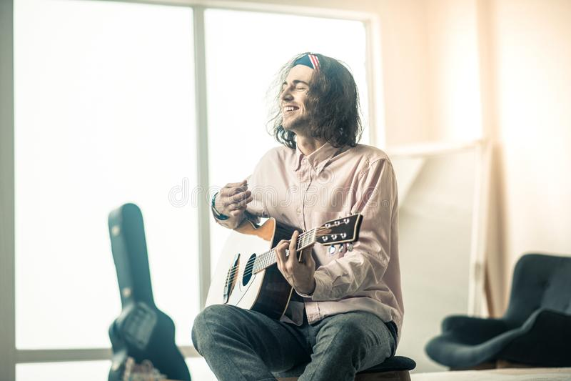 Vrolijke knappe jonge gitaristzitting in heldere ruimte royalty-vrije stock afbeelding