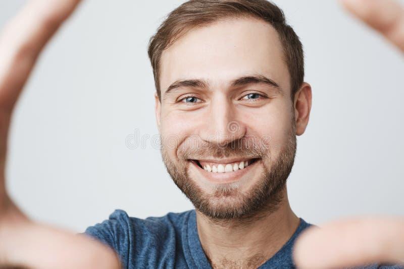 Vrolijke knappe jonge mens die in blauw overhemd met donker haar, positief nieuws ontvangen gelukkig glimlachen die Aantrekkelijk royalty-vrije stock fotografie