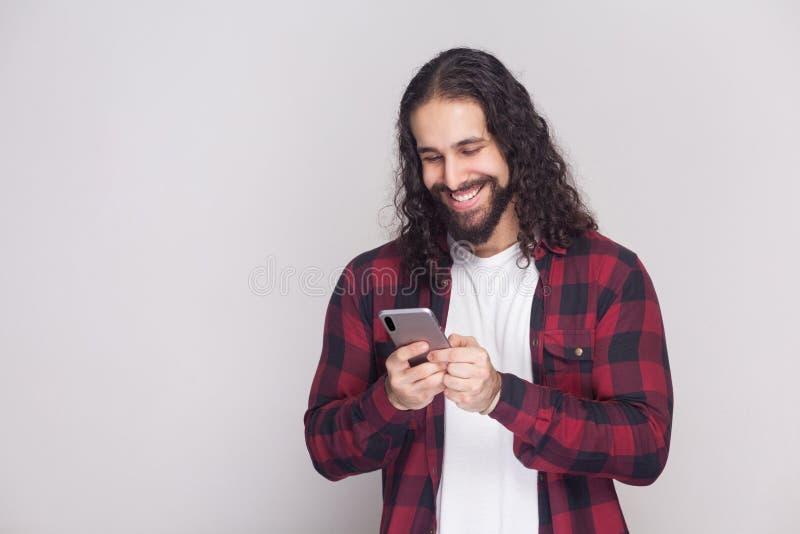 Vrolijke knappe jonge mens in rood geruit overhemd en lange krul royalty-vrije stock afbeelding