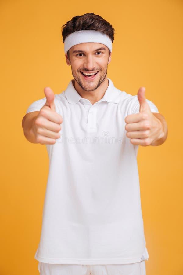 Vrolijke knappe jonge sportman die duimen met beide handen tonen royalty-vrije stock foto's