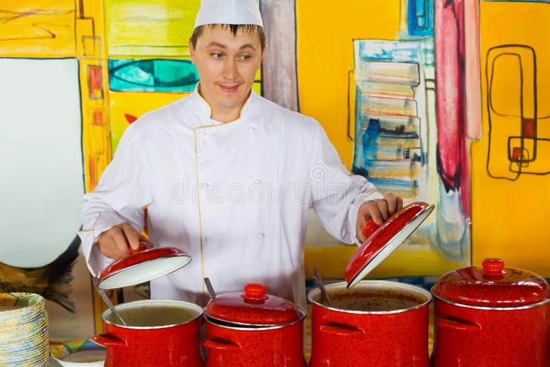 Vrolijke kok dichtbij rode pannen in openbaar restaurant stock afbeeldingen