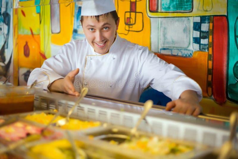 Vrolijke kok in eenvormige dichtbijgelegen teller met maaltijd royalty-vrije stock fotografie