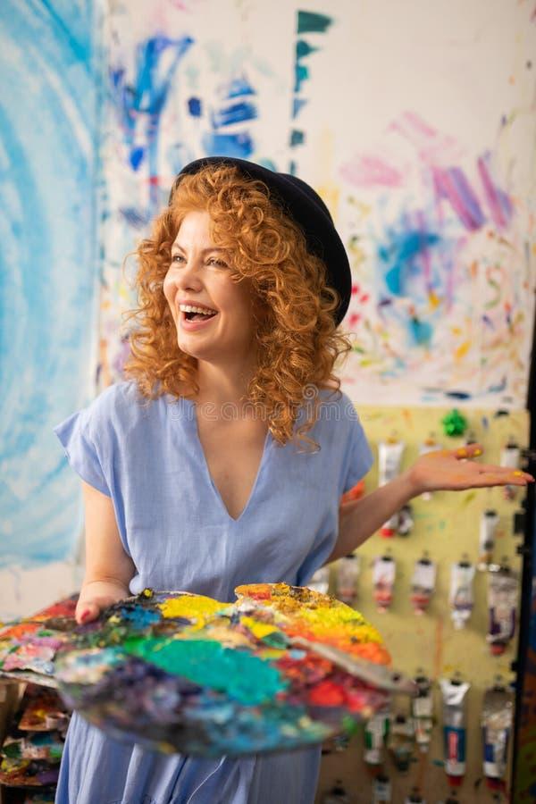 Vrolijke krullende roodharige kunstenaar die gelukkig terwijl het schilderen voelen royalty-vrije stock foto