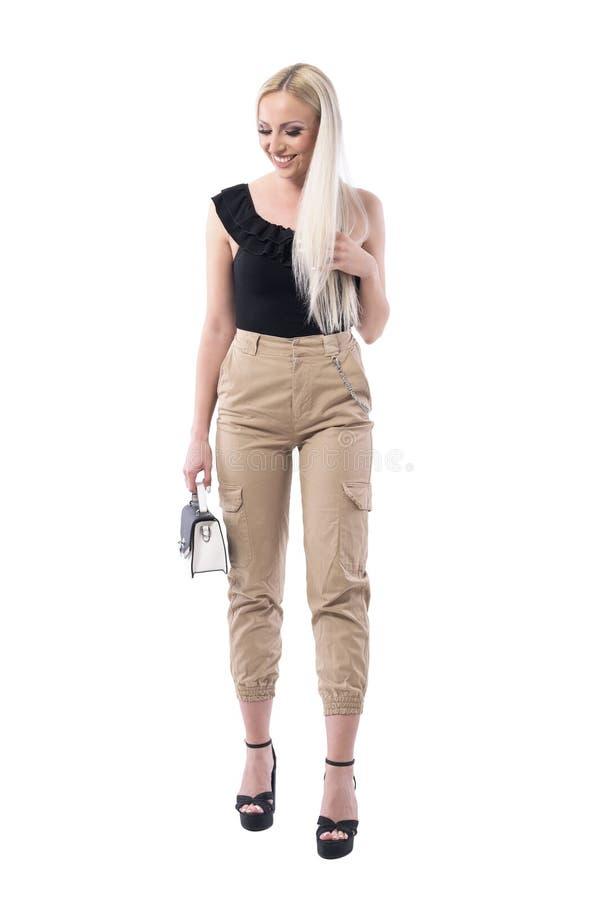 Vrolijke lachende mooie blondevrouw in de kleren van de straatstijl met handtas royalty-vrije stock afbeelding