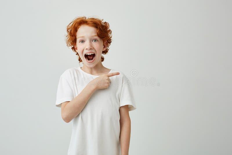 Vrolijke leuk weinig jongen met het krullende van gemberhaar en sproeten gelukkige glimlachen en het richten opzij met vinger op  stock foto