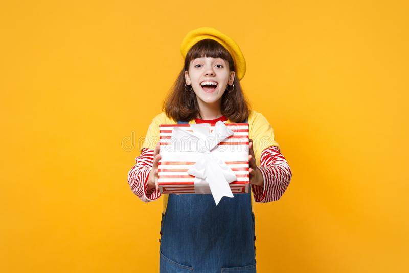 Vrolijke leuke meisjestiener in Franse baret, de rode gestreepte huidige doos van de denim sundress holding met geïsoleerd giftli stock foto
