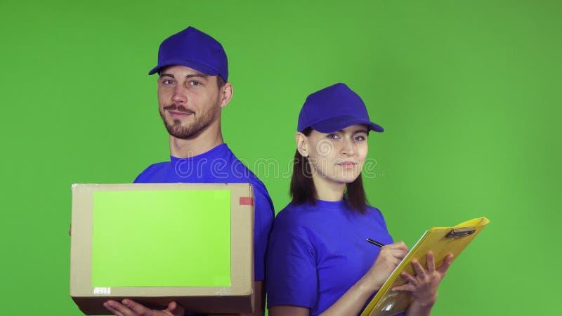Vrolijke leveringsarbeiders met een pakket die aan de camera glimlachen royalty-vrije stock foto's