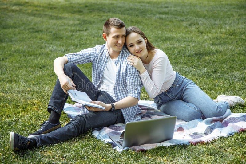 Vrolijke man en vrouw die in aard na het leren rusten royalty-vrije stock fotografie