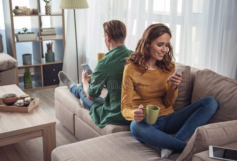 Vrolijke man en vrouw die rust met smartphones hebben stock fotografie