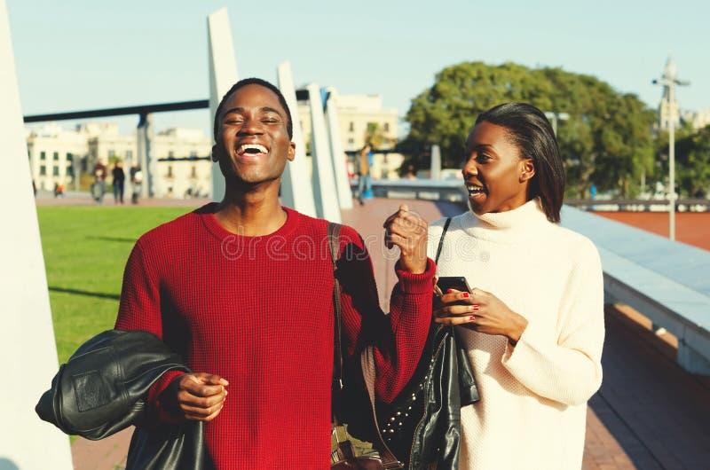 Vrolijke man en vrouwen universitaire studenten die op campus, jong modieus mannelijk en wijfje lopen die tijdens de onderbreking royalty-vrije stock afbeelding