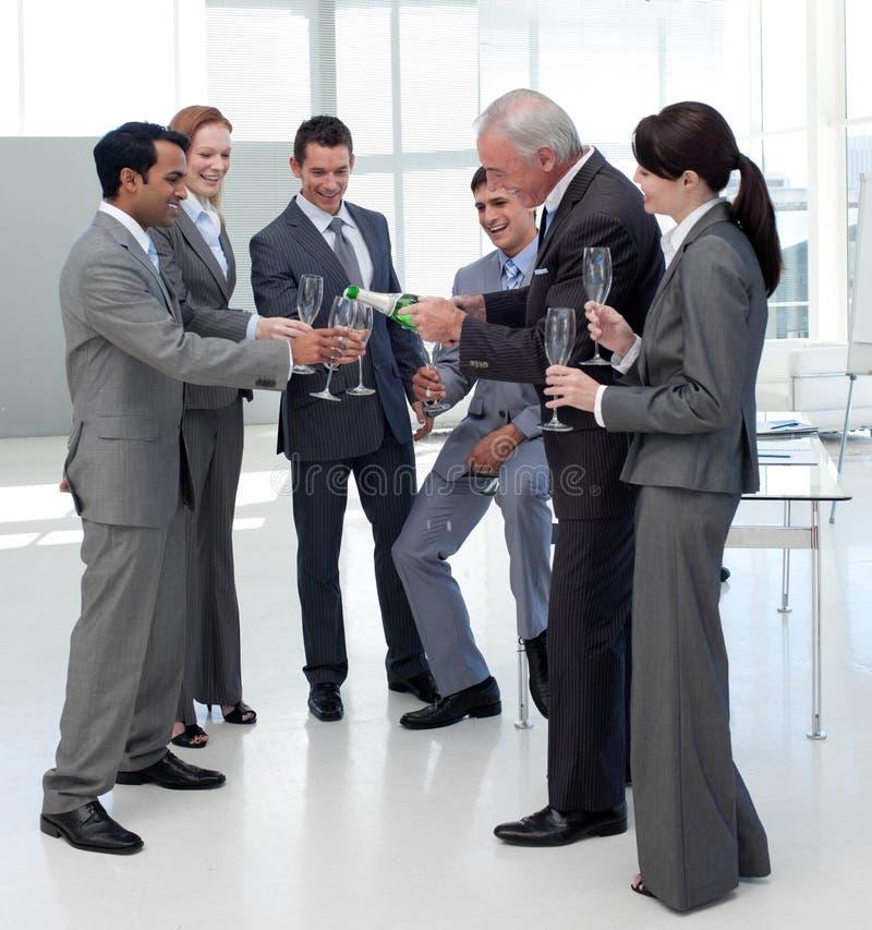 Vrolijke manager die Champagne dient aan zijn team royalty-vrije stock foto