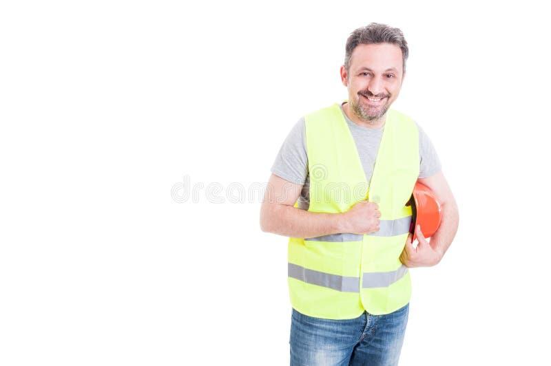 Vrolijke mannelijke aannemer die zijn beschermingshelm houden stock afbeeldingen