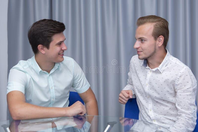 Vrolijke mannelijke bus in vrijetijdskleding die informatie verklaren aan het jonge werknemer glimlachen en tijdens positieve med royalty-vrije stock afbeeldingen