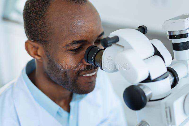Vrolijke mannelijke tandarts die een professionele microscoop gebruiken stock fotografie
