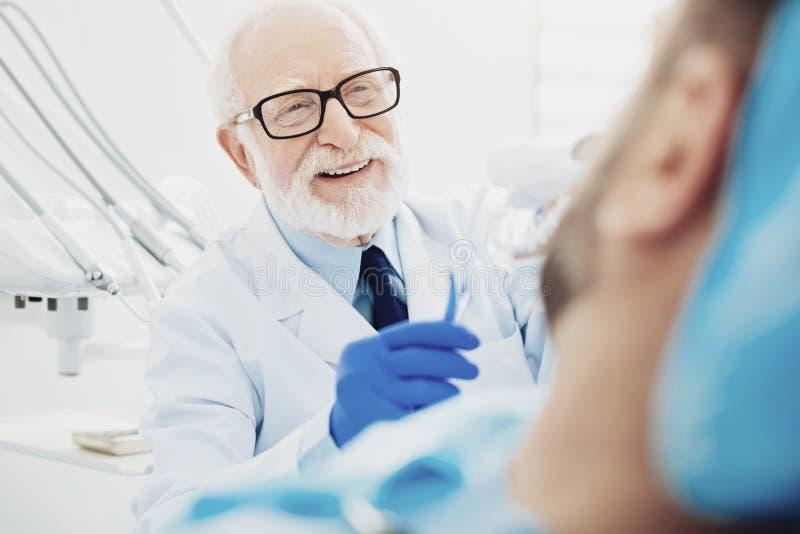 Vrolijke mannelijke tandarts die tanden het schoonmaken tonen stock afbeeldingen