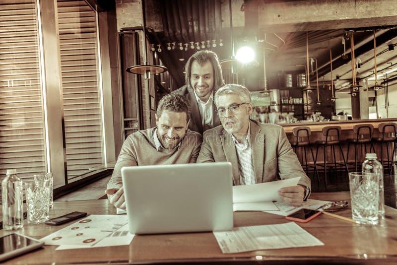 Vrolijke mannetjes die bij het scherm van laptop staren stock foto