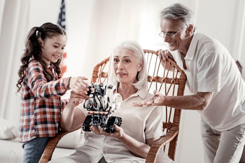 Vrolijke meisje en opa die robot tonen aan oma stock afbeelding