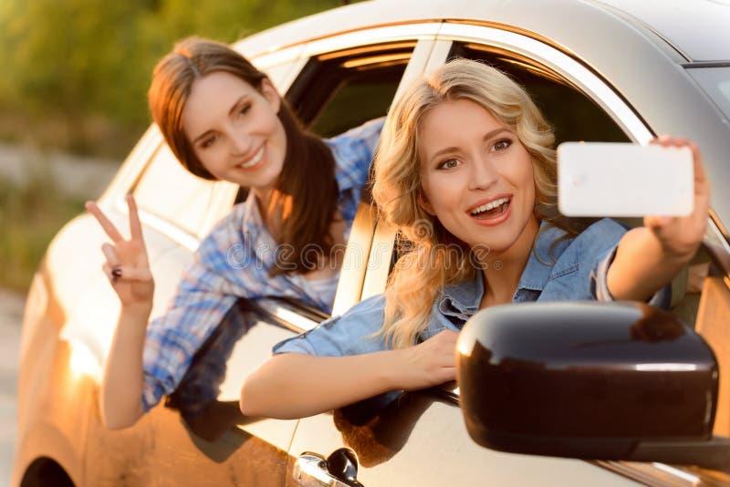 Vrolijke meisjes die in de auto zitten stock foto's