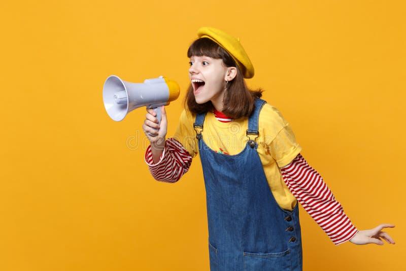 Vrolijke meisjestiener in Franse baret, denim die sundress die, schreeuw in megafoon opzij eruit zien op gele muur wordt geïsolee stock afbeeldingen