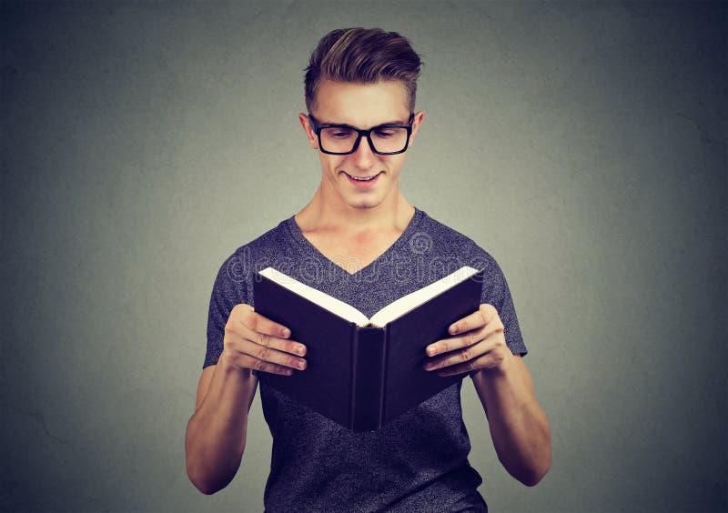 Vrolijke mens die een boek lezen stock foto