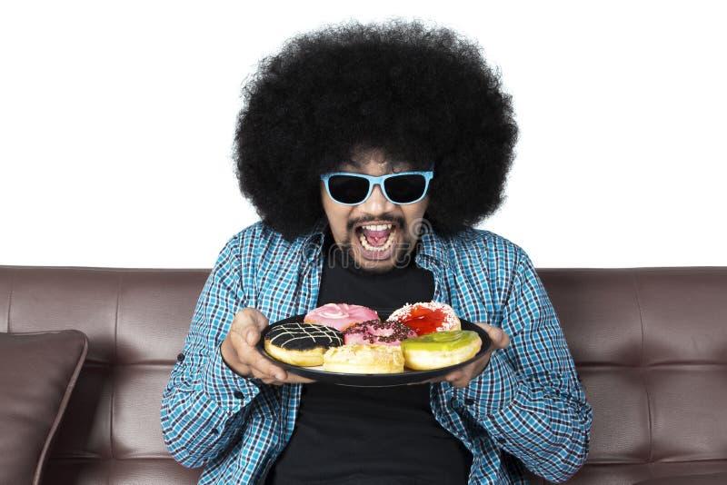 Vrolijke mens die een plaat van donuts houden stock foto