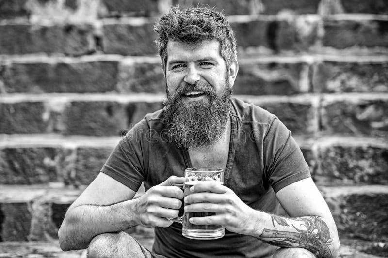 Vrolijke mens die met bier in zijn handen op steentrap binnen zitten de stad in Glimlachende jonge mens met modieuze baard stock foto