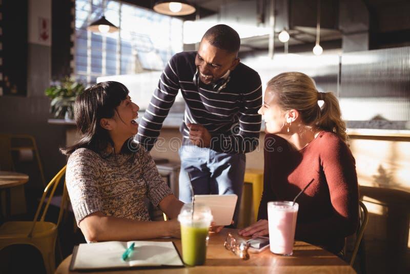 Vrolijke mens die met vrouwelijke vrienden bij koffiewinkel spreken stock foto