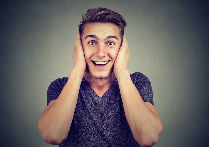 Vrolijke mens die oren in verrassing behandelen stock fotografie