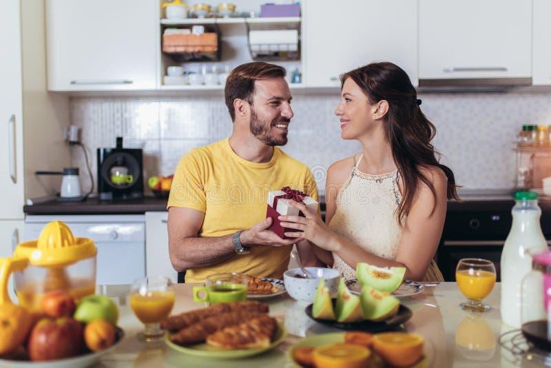 Vrolijke mens die zijn meisje met een gift thuis in de keuken verrassen terwijl ontbijt stock afbeeldingen