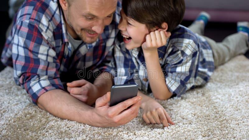 Vrolijke mens en jongen die na het letten van op grappige video op smartphone, vreugde lachen stock foto's