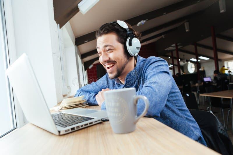 Vrolijke mens in hoofdtelefoon die laptop met behulp van stock afbeeldingen