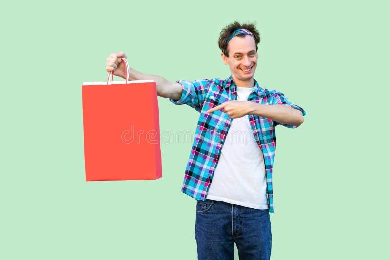 Vrolijke moderne jonge volwassen mens in witte t-shirt en geruit overhemd die en vinger bevinden richten zich aan het winkelen za royalty-vrije stock afbeeldingen