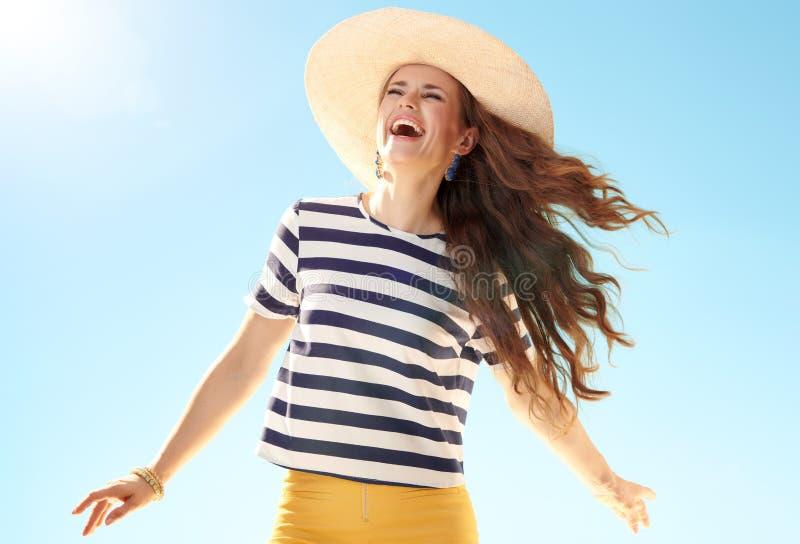 Vrolijke moderne vrouw in strohoed tegen blauwe hemel stock foto