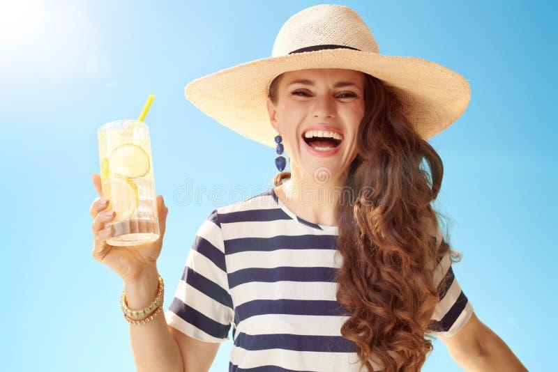 Vrolijke moderne vrouw tegen blauwe hemel met het verfrissen van cocktail stock afbeelding