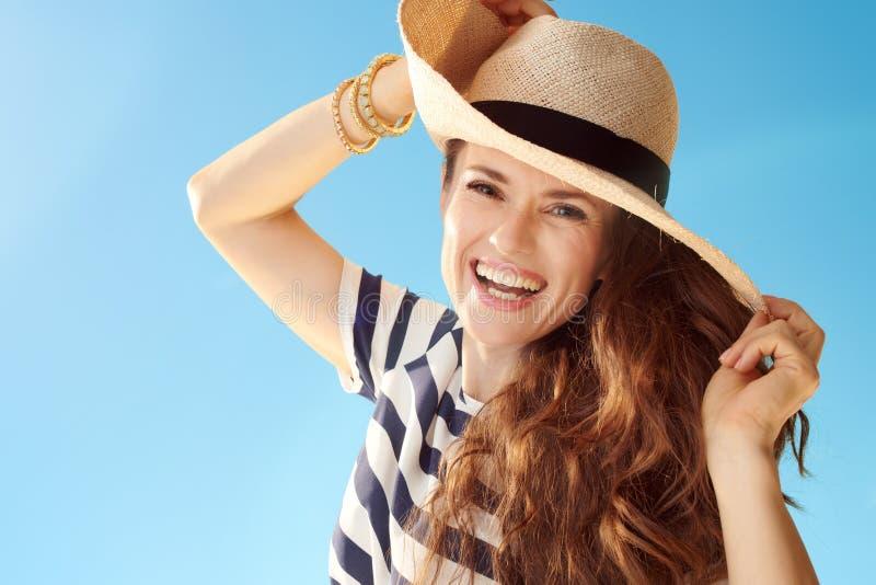 Vrolijke moderne vrouw tegen het blauwe hemel spelen met strohoed stock foto's