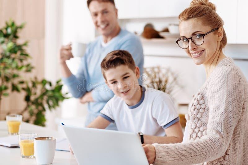 Vrolijke moeder die haar zoon met thuiswerk helpen stock afbeelding