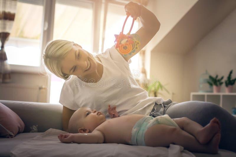 Vrolijke moeder die met haar weinig babyjongen thuis beoefenen stock foto
