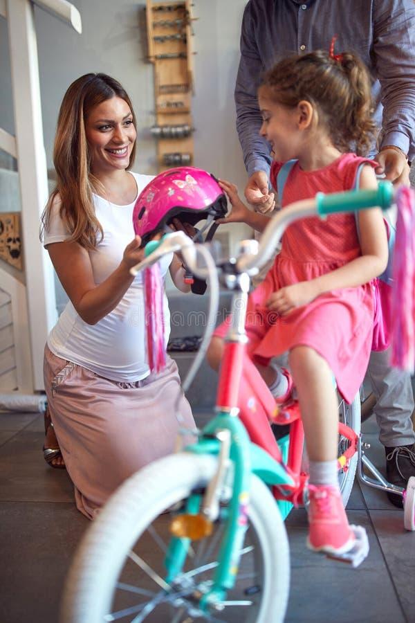 Vrolijke moeder die nieuwe fiets en helm kopen voor meisje in fietswinkel stock foto