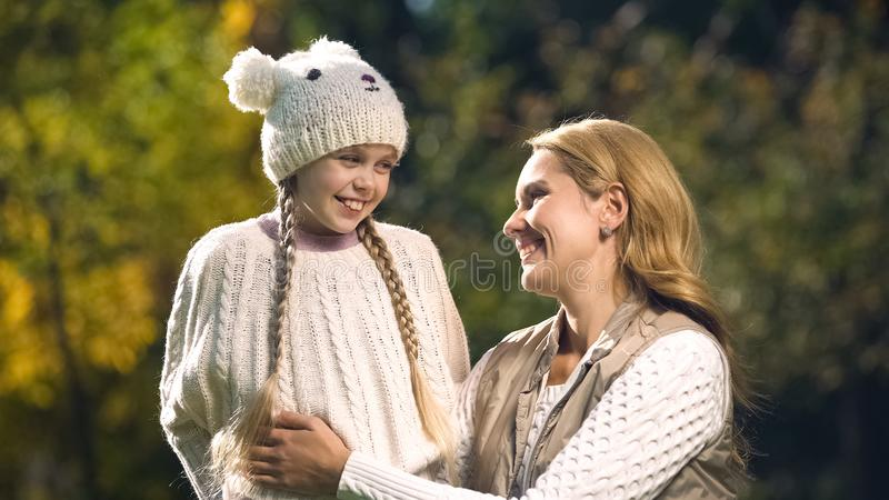 Vrolijke moeder en dochter die elkaar in de herfstpark bekijken, moederschap stock afbeelding