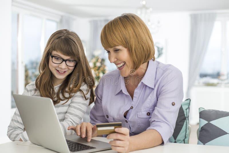 Vrolijke moeder en dochter die online thuis tijdens Kerstmis winkelen stock afbeelding