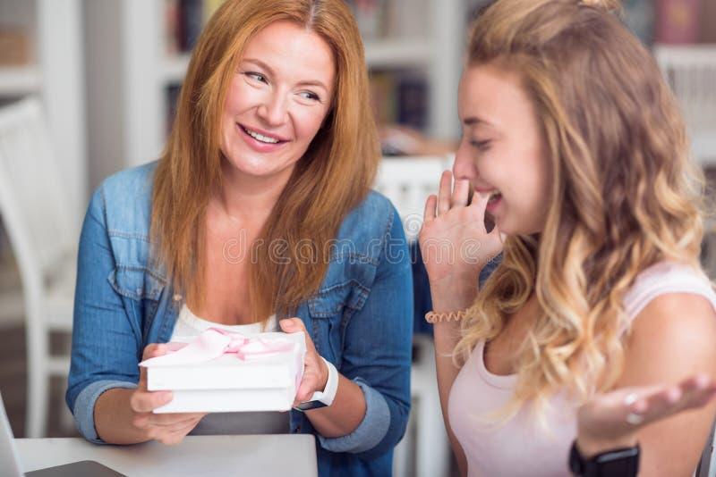 Vrolijke moeder en dochterzitting in de koffie stock fotografie