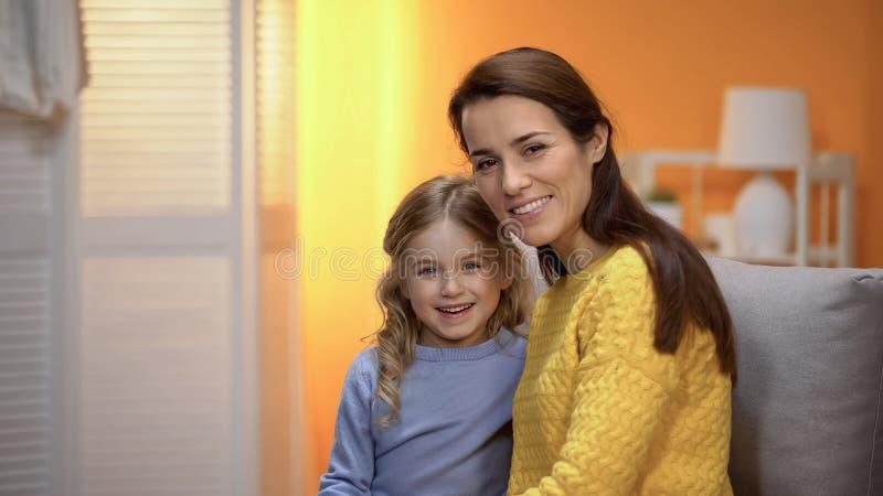 Vrolijke moeder en weinig dochter die en aan camera, reclame glimlachen kijken stock foto's