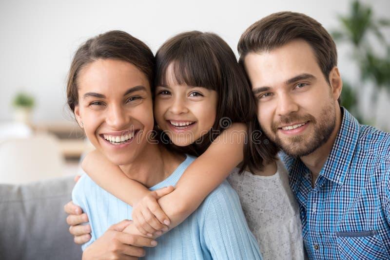 Vrolijke mooie familie van drie die het lachen het bekijken omhelzen stock fotografie